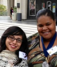 Two girls of color smiling into the camera. Both are wearing badges. One is wearing a medal.