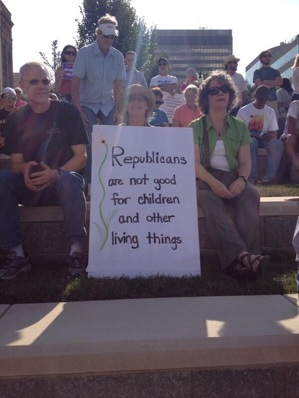 A man and woman sitting beside a woman holding a sign that says Republicans are not good for children and other living things