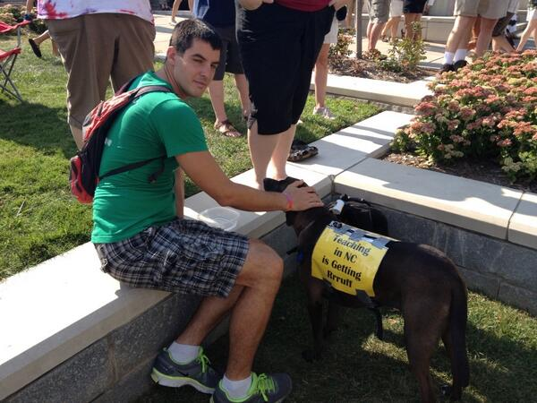 """Man petting dog which has a sign taped to it saying """"Teaching in NC is getting rrrruff."""""""